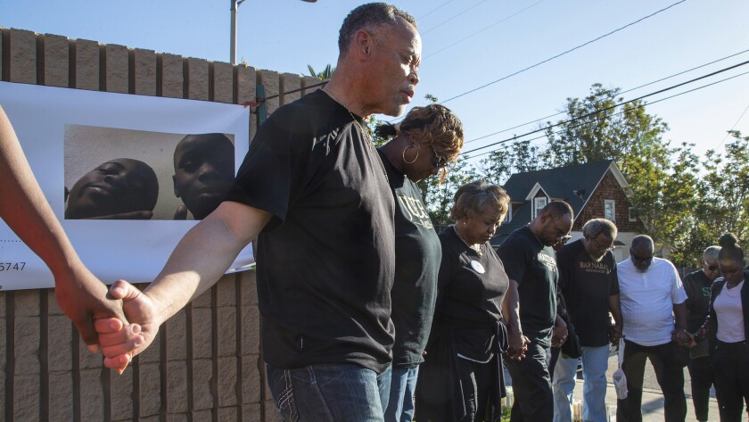 Pastor Joshua Beckley of Ecclesia Christian Fellowship leads community members in prayer at a memorial for shooting victim Jason Spears, 12, who was shot while buying a bag of chips.
