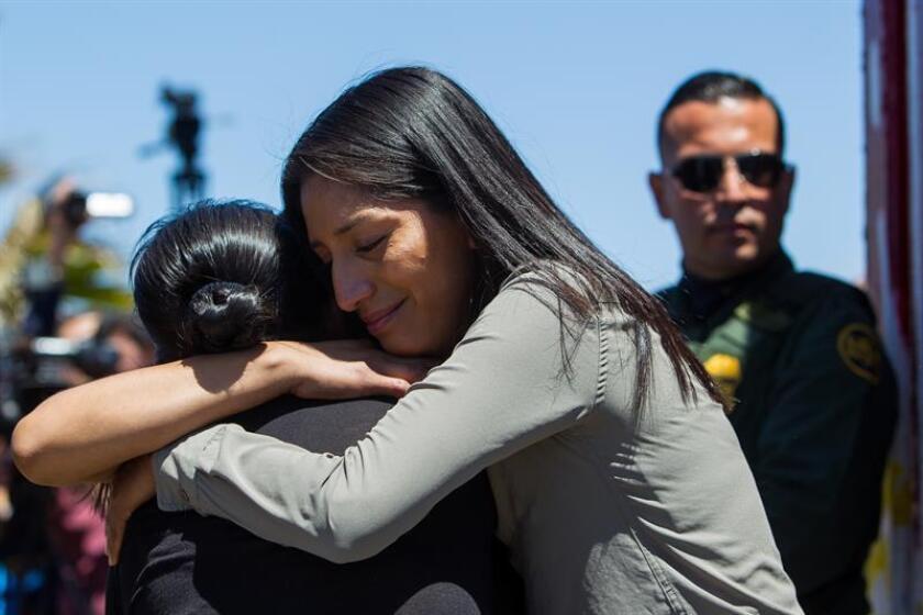 Miembros de una familia se abrazan junto a un guardia fronterizo en la frontera de Tijuana (México) y San Diego (California). EFE/Archivo