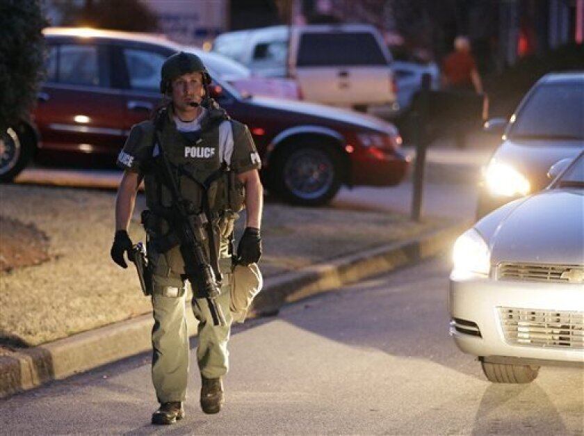 A police officer leaves the scene after an explosion and gunshots were heard near the scene where a man was holding four firefighters hostage Wednesday, April 10, 2013 in Suwanee, Ga. A police spokesman said the suspect was dead and none of the hostage suffered serious injuries.  (AP Photo/John Baz