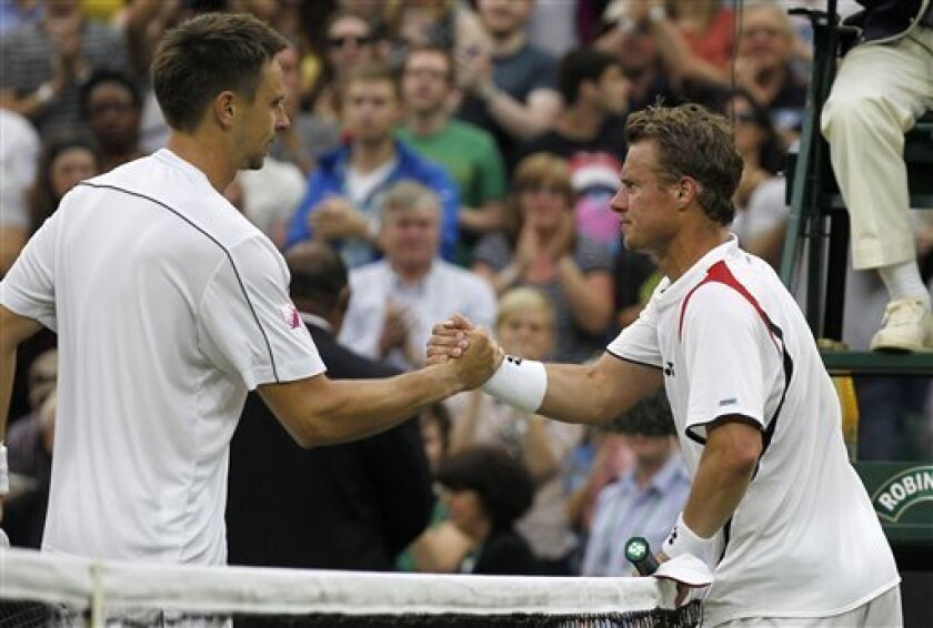 Sweden's Robin Soderling, left, shakes hands after defeating Australia's Lleyton Hewitt at the All England Lawn Tennis Championships at Wimbledon, Thursday, June 23, 2011. (AP Photo/Anja Niedringhaus)