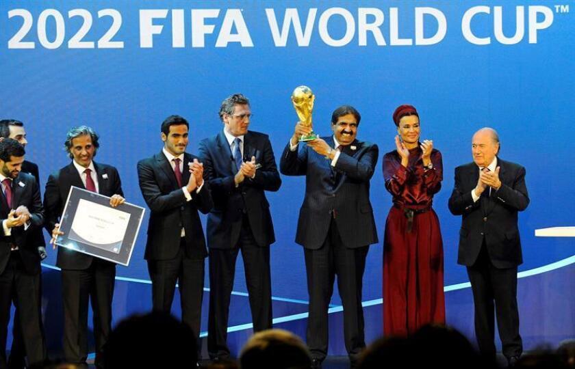 El Emir de Qatar, jeque Hamad bin Khalifa Al-Thani (i), recibe el trofeo del Mundial de fútbol de manos del ex presidente de la FIFA, Joseph S. Blatter (d), tras la elección de Qatar como país organizador del Mundial de Fútbol 2022. EFE/Archivo