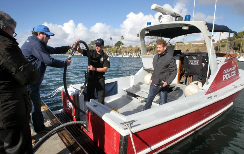 At the new state-of-the art bilge pump out and oil-water separator station at the Oceanside Harbor Oceanside Police Officer Mark Bussey, middle, hands the pump hose to Art Bleier, left, that Mark used to pump bilge water from an Oceanside Police harbor patrol boat. At right is Alex Bleier. Alex and Art are from Keco Pump and Equipment, of San Diego, the maker of the system.