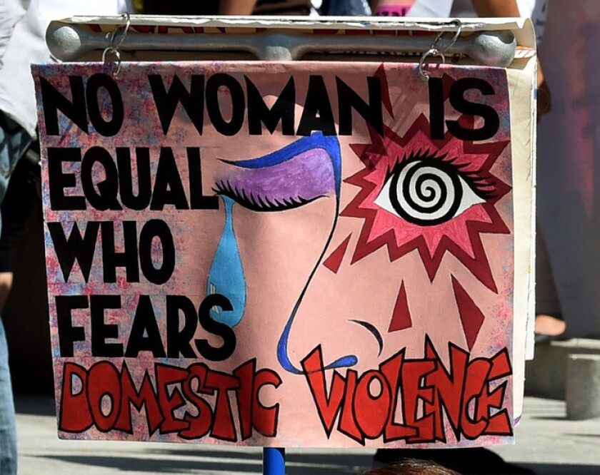 """A sign at a rally in 2015 reads """"No woman is equal who fears domestic violence"""""""