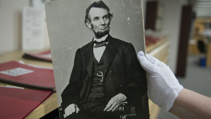A woman holds a photograph of President Abraham Lincoln at the National Archives in College Park, Md. on April 6, 2015.