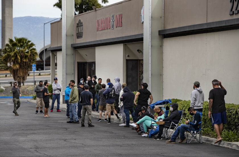 Customers wait in line Tuesday to buy guns at Warrior One Guns and Ammo in Riverside.