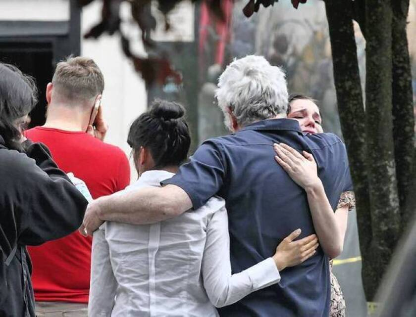 People console one another outside Cafe Racer, the site of the first Seattle shooting on Wednesday. The same gunman is believed to have killed a woman in a carjacking before turning his gun on himself.