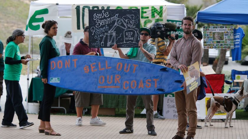 Arlis Reynolds, left, and Rob Moddelmog hold a surfboard while Cody Parole holds a sign against the