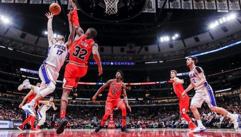 Kris Dunn (d) de Chicago Bulls en acción con JJ Redick (i) de Philadelphia 76ers durante un partido de baloncesto de la NBA disputado, en el United Center de Chicago, Illinois (EE.UU.). EFE