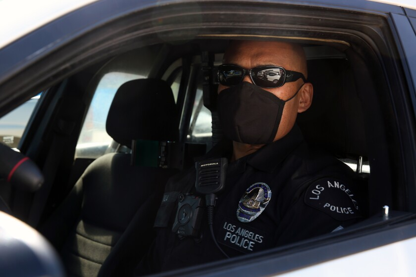 Officer Junior Nua sets out in his car wearing a black cloth mask at LAPD Harbor Station in San Pedro.  Officers have been issued two cloth masks and are required to take their temperature on entering work to make sure they are healthy.