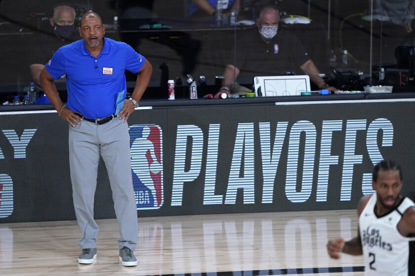 Los Angeles Clippers head coach Doc Rivers stands on the sideline with hands on hips.