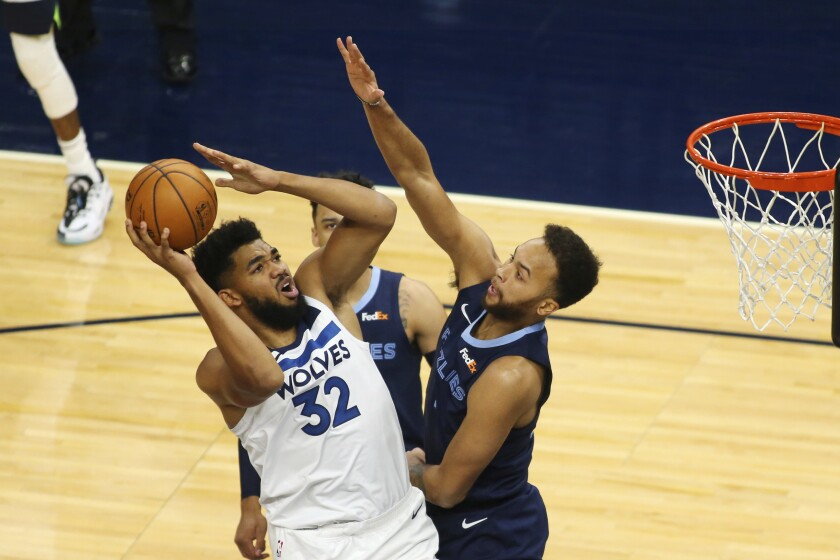 Minnesota Timberwolves forward Karl-Anthony Towns (32) shoots against Memphis Grizzlies forward Kyle Anderson, right, and guard Dillion Brooks in the first quarter during an NBA preseason basketball game, Saturday, Dec. 12, 2020, in Minneapolis. (AP Photo/Andy Clayton- King)