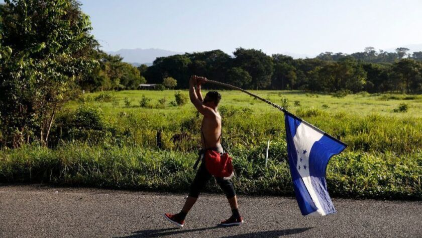 A Honduran migrant carries his national flag on Oct. 25 as he walks north near Mapastepec, Mexico, as part of a caravan trying to reach the United States, still more than 1,000 miles away.
