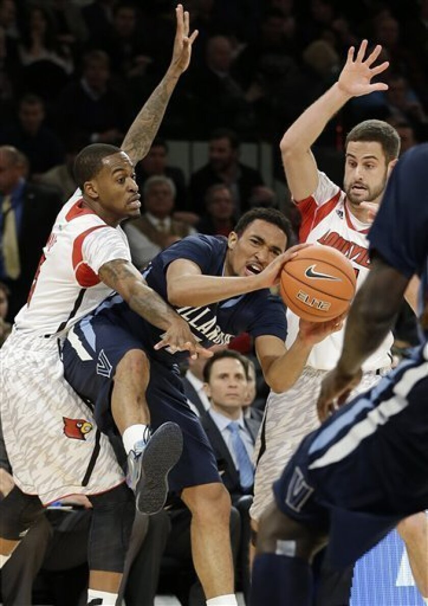 Villanova's Darrun Hilliard, center, looks to pass away from Louisville's Kevin Ware, left, and Luke Hancock during the second half of an NCAA college basketball game at the Big East Conference tournament, Thursday, March 14, 2013, in New York. (AP Photo/Frank Franklin II)