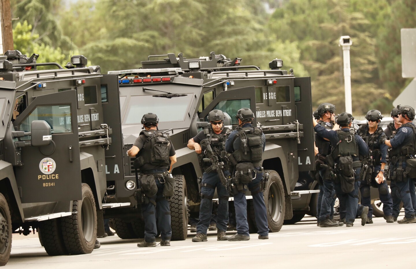 LAPD SWAT swarms area near a Orange line bus at Victory and Woodley where victim was shot by possible gunman being sought by LAPD for killing his family early today in Canoga Park.