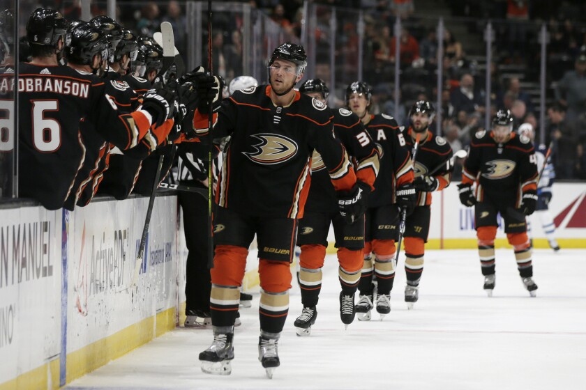 Ducks defenseman Cam Fowler, center, gets congratulations from teammates after scoring against the Winnipeg Jets during the first period on Tuesday at Honda Center.
