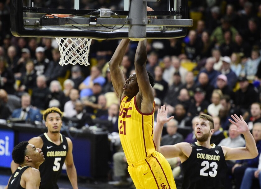 Colorado's Tyler Bey, left, D'Shawn Schwartz, and Lucas Siewert, look on as USC's Onyeka Okongwu dunks during the first half on Thursday in Boulder, Colo.