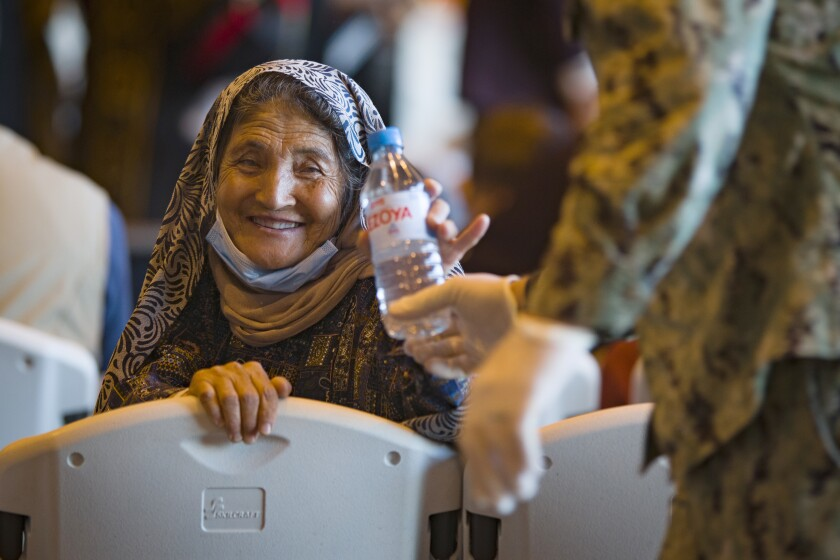 A woman holds a bottle of water and smiles.