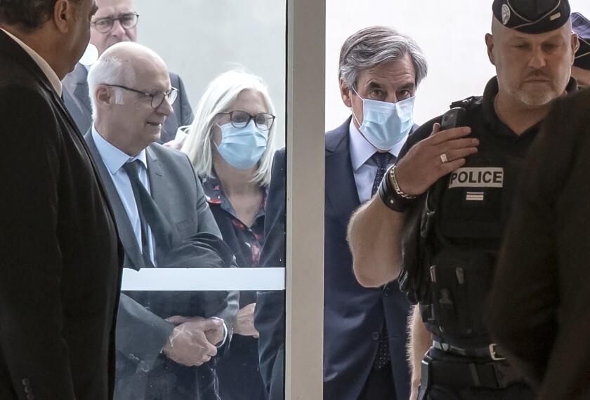 El exprimer ministro francés Francois Fillon, derecha, y su esposa Penelope, centro, portan cubrebocas a su llegada a la corte en París, el lunes 29 de junio de 2020. (AP Foto/Michel Euler)