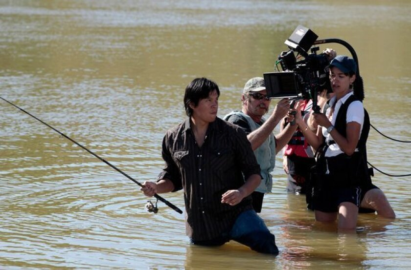 """The camera follows lead actor Chaske Spencer into the water during filming of """"Winter in the Blood"""" near Chinook, Mont., in 2011."""
