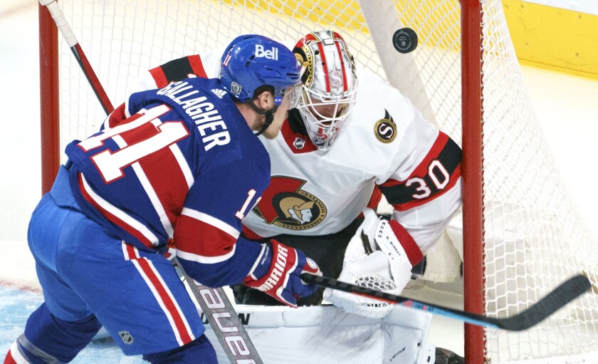 Ottawa Senators goaltender Matt Murray, right, loses sight of the puck as Montreal Canadiens' Brendan Gallagher waits for the rebound during second-period NHL hockey game action in Montreal, Thursday, Feb. 4, 2021. (Paul Chiasson/The Canadian Press via AP)