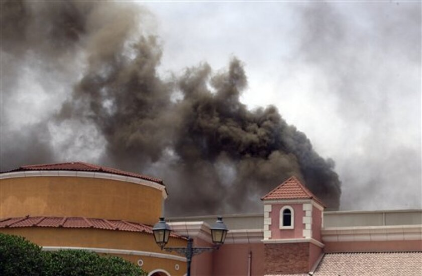 Smoke rises above the Villaggio Mall, in Doha's west end, as a fire took hold of the upscale mall in the Qatari capital of Doha Monday May 28, 2012. Qatar's Interior Ministry said 13 children were among 19 people killed in a fire that broke out at one of the Gulf state's fanciest shopping mall on M
