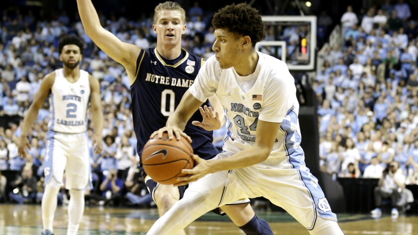 North Carolina's Justin Jackson prepares to pass as he's defended by Notre Dame's Rex Pflueger (0) defends during the first half Sunday.