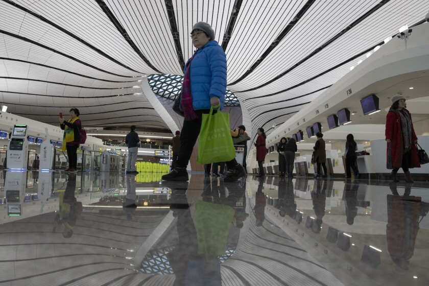 Visitors past through the Beijing Daxing International Airport near Beijing on Wednesday, Dec. 11, 2019. Newly opened in Sept, the airport was built in less than five years at a cost of 120 billion yuan (dollars 17 billion U.S.), is designed to handle 72 million passengers a year. (AP Photo/Ng Han Guan)