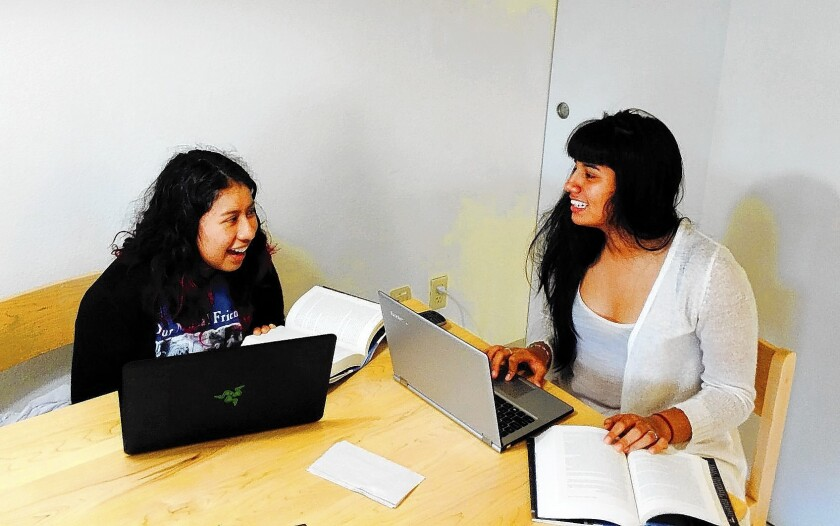 High school students Kenia Coyoy, left, and Karen Molina compare ideas at the Dickens Universe conference at UC Santa Cruz.