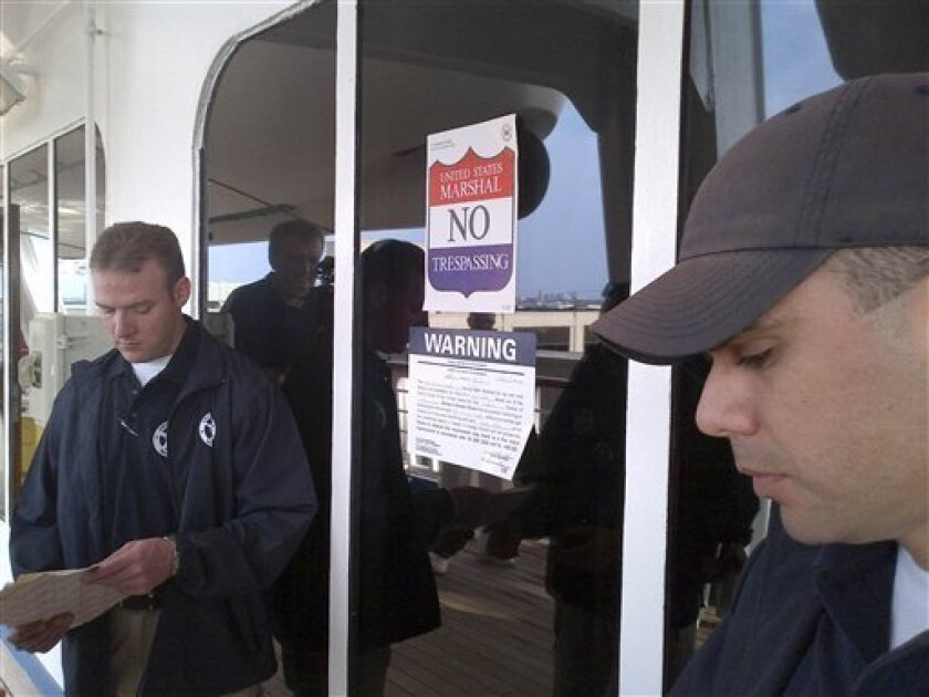 In this picture provided by the Eaves Law Firm on Saturday, March 31, 2012, unidentified US Marshals are seen enforcing an arrest warrant on board of the Carnival Triumph cruise ship moored at Galveston harbor, TX, U.S.A., Saturday, March 31, 2012. An arrest warrant was issued on Friday for the MS