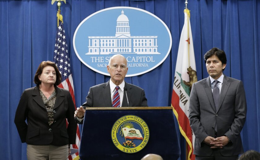 Calif. Gov. Jerry Brown, flanked by Assembly Speaker Toni Atkins, D-San Diego, left, and Senate President Pro Tem Kevin de Leon, D-Los Angeles, announced scaling back their climate change proposal during a Sept. 9 news conference in Sacramento.