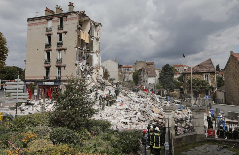French firefighters search the rubble of a collapsed building in Rosny-Sous-Bois