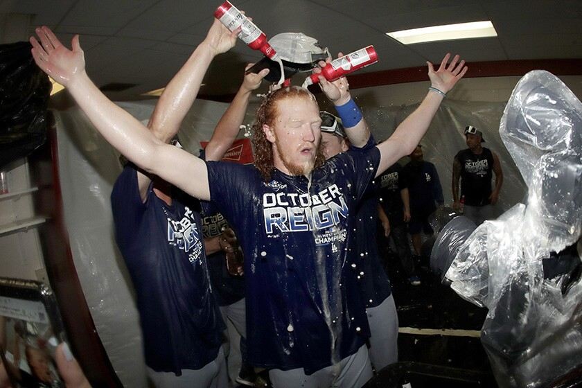 Dustin May is doused during a locker room celebration after the Dodgers clinched their seventh consecutive NL West title.