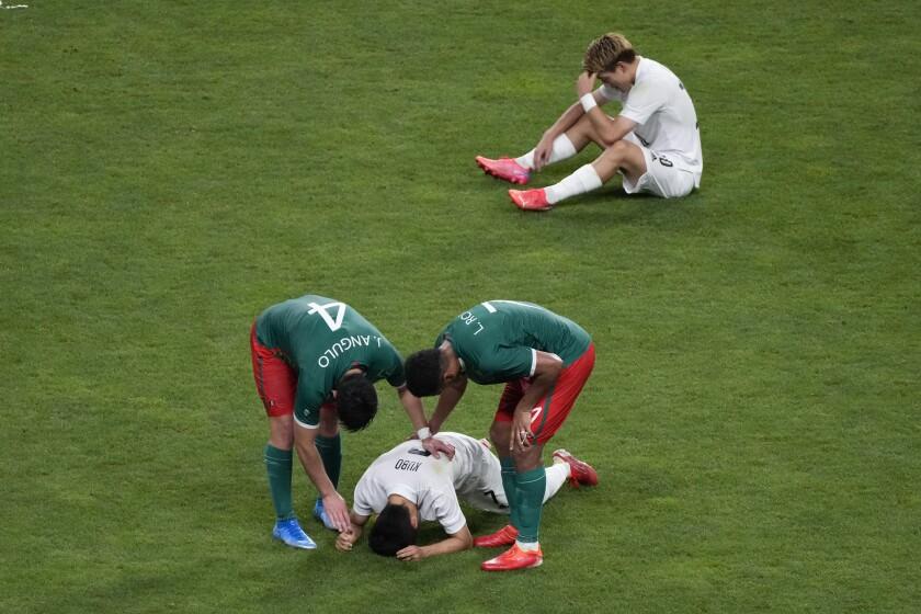 ARCHIVO - En esta foto del 6 de agosto de 2021, Jesús Angulo (4) y Luis Romo, de la selección de México.