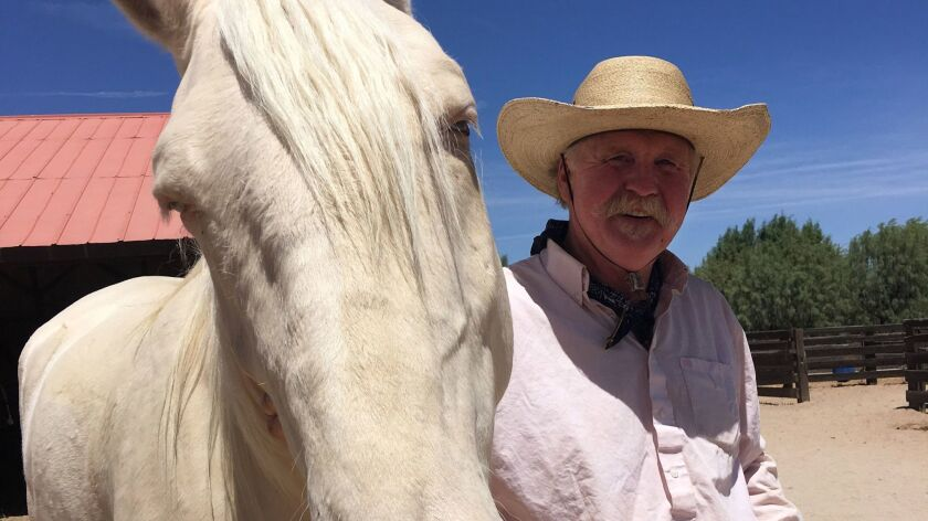 The Colonel, head wrangler Paul Vance, with his trusty steed, Topper.