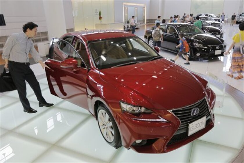 A visitor looks at a Lexus IS300h displayed at Toyota Motor Corp.'s showroom Toyota Mega Web in Tokyo Friday, Aug. 2, 2013. Toyota nearly doubled its April-June profit from a year ago to 562.1 billion yen ($5.5 billion), getting a big boost from a cheap yen. (AP Photo/Itsuo Inouye)
