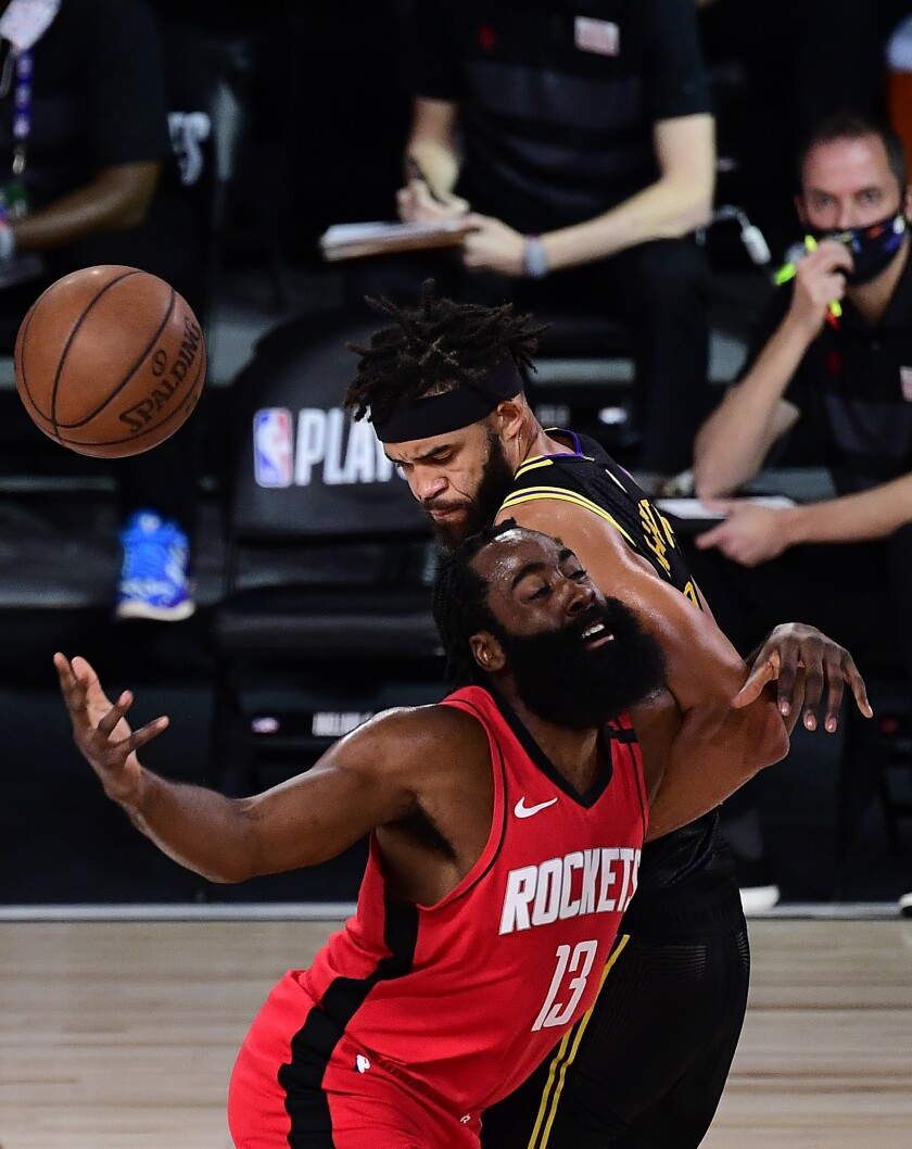 James Harden of the Houston Rockets is defended by JaVale McGee of the Lakers.