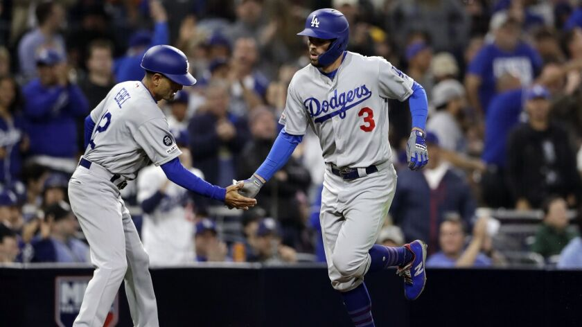 Chris Taylor is congratulated by Dodgers third base coach Dino Ebel after hitting a home run earlier this season.