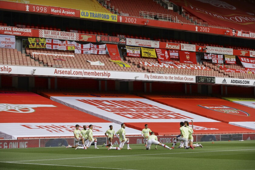 Arsenal players warm up prior the English Premier League soccer match between Arsenal and Norwich City at the Emirates Stadium in London, England, Wednesday, July 1, 2020. (Richard Heathcote/Pool via AP)
