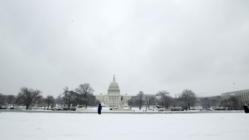 People walk outside of the U.S. Capitol building during a snowstorm, as a partial government shutdow