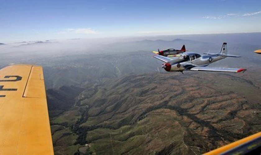 Mike Polley flew his 1946 North American Navion (right), and Jim Munn piloted his 1943 SNJ-4 (far right) as part of yesterday's formation-flying clinic. Photo taken from a T-6 Texan flown by Pete Hunt. (Eduardo Contreras / U-T)