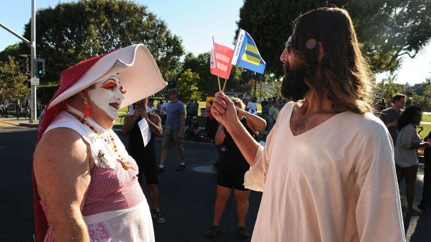 WEST HOLLYWOOD, CALIFORNIA JUNE 26, 2013-A drag queen and a man dressed like jesus talk before a ral