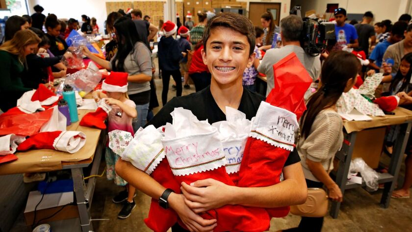 Kenan Pala, 13, of Rancho Bernardo with some of the Christmas stockings stuffed with donated toys and personal items Sunday by volunteers with his nonprofit group Kids 4 Community.