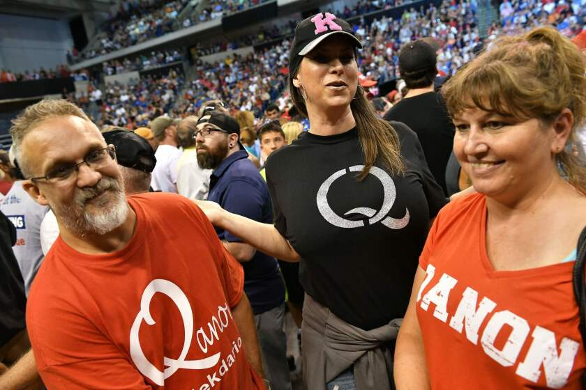 """Members of QAnon await the arrival of US President Donald Trump for a political rally at Mohegan Sun Arena in Wilkes-Barre, Pennsylvania on August 2, 2018. QAnon adheres to a grand-scale conspiracy theory placing President Trump against an alleged """"deep state"""" committed to to ending his rule."""