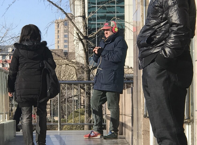 CNN cameraman outside a train station in Beijing