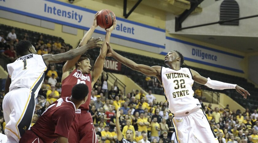 Alabama guard Dazon Ingram (12) fights for the ball with Wichita State forward Zach Brown (1) and forward Markis McDuffie (32) during the first half of an NCAA college basketball game Friday, Nov. 27, 2015, in Orlando, Fla. (AP Photo/Willie J. Allen Jr.)