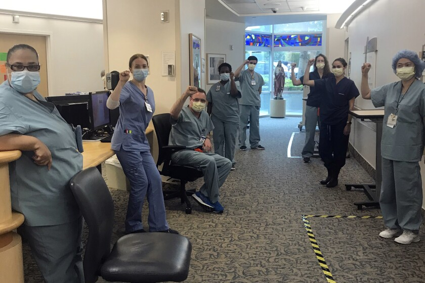 Nurses at Providence St. John's Health Center in Santa Monica raise their fists April 10 in solidarity after telling managers they can't care for COVID-19 patients without N95 masks.