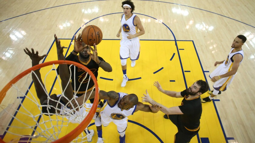Cleveland Cavaliers forward LeBron James goes to the basket and Golden State Warriors defend during the seventh NBA Finals game June 19.