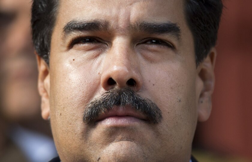 FILE - I this March 17, 2015, file photo, Venezuela's President Nicolas Maduro listens to the playing of national hymns as he welcomes regional leaders to Miraflores presidential palace for an emergency ALBA meeting in Caracas, Venezuela. On Thursday, Oct. 5, 2015, Maduro repeated a promise to shav