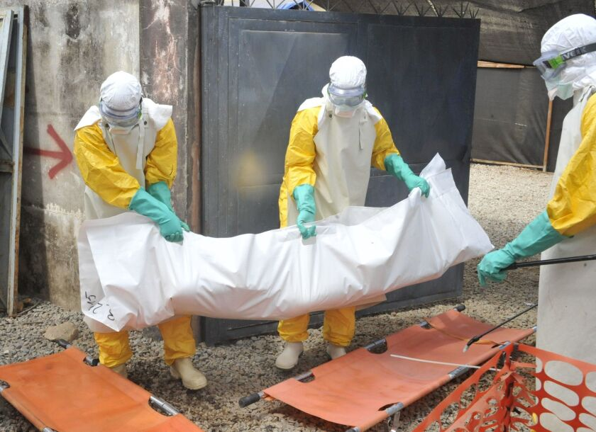 Members of the Guinean Red Cross carry the body of a person who died from the Ebola virus in Conakry in March. A study conducted there could not find evidence that transfusions of blood plasma from Ebola survivors helped patients recover from the disease.