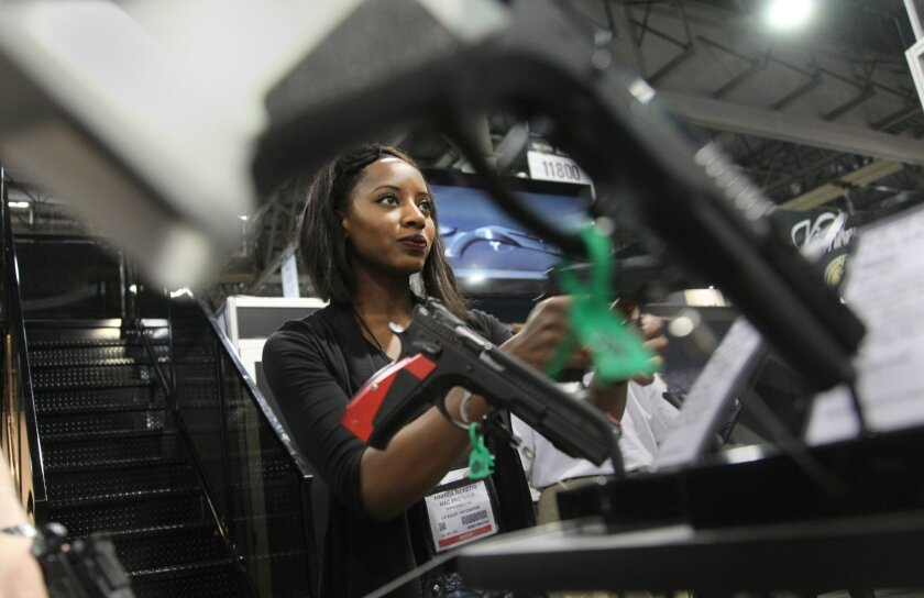 Amanda Ricketts of Mac Pro Shop in Springfield, Missouri checks out the selection of handguns at the CZ-USA showroom at the SHOT show.